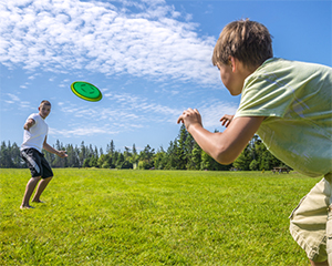 two boys playing frisbee in a field blue sky with cloud trails