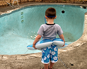boy with rubber ring stands by empty disused swimming pool