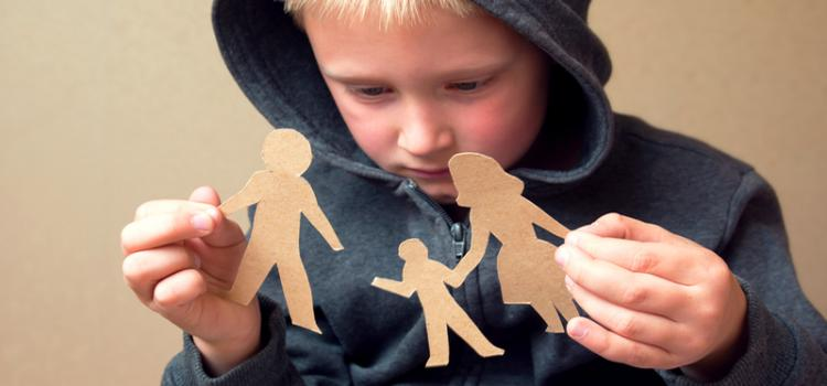Small boy holds broken paper cutout family
